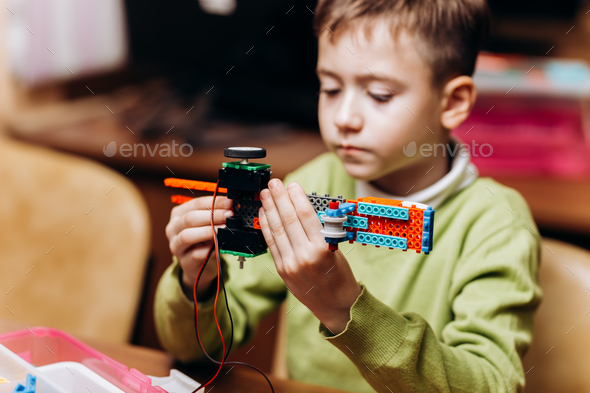 Boy dressed in green sweater sits at the table in the robotics school and makes a robot from the - Stock Photo - Images