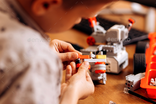 Smart boy dressed in gray shirt makes a robot from the robotic constructor at the desk in the School - Stock Photo - Images