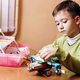 Boy dressed in green sweater sits at the desk with computer and looks at the robot that he made from - PhotoDune Item for Sale