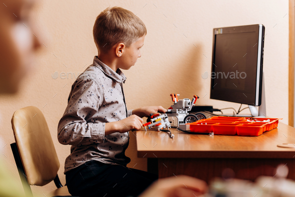 Diligent boy dressed in gray shirt makes a robot from the robotic constructor at the desk with - Stock Photo - Images