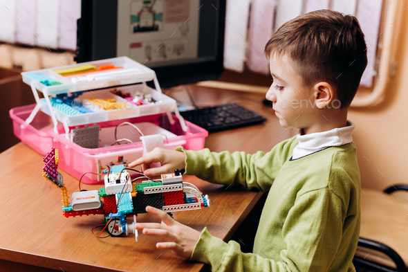 Diligent boy dressed in green sweater sits at the desk with computer and makes the robot from the - Stock Photo - Images