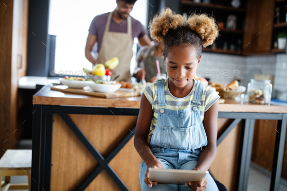 Cute african american girl using a tablet while her parents preparing food in kitchen - Stock Photo - Images