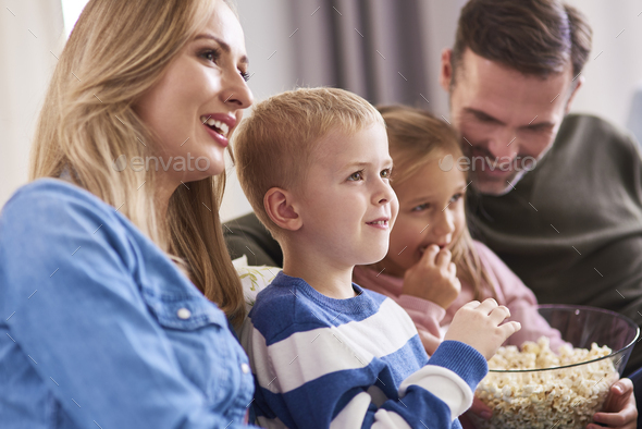 Close up of family watching tv at home - Stock Photo - Images