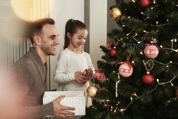 Girl and her daddy decorating Christmas tree - Stock Photo - Images