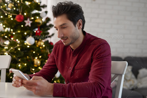 Man with mobile phone sending the best wishes for Christmas - Stock Photo - Images