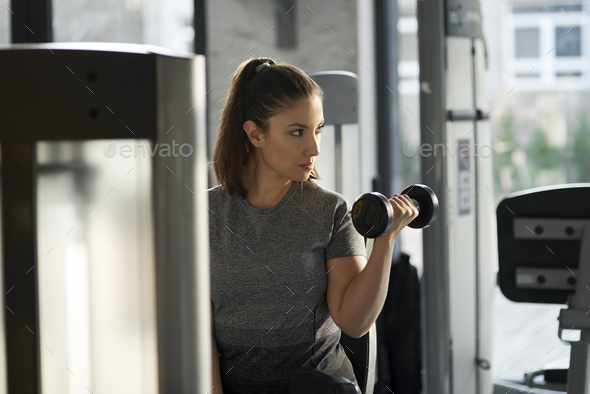 Young woman practicing with dumbbell at the gym - Stock Photo - Images