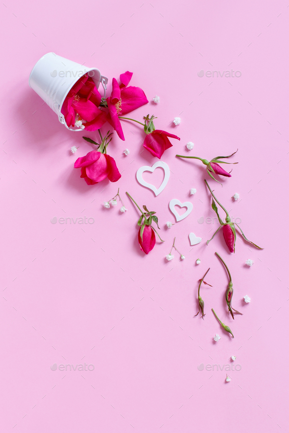 Spring composition with pink flowers and hearts falling from bucket - Stock Photo - Images