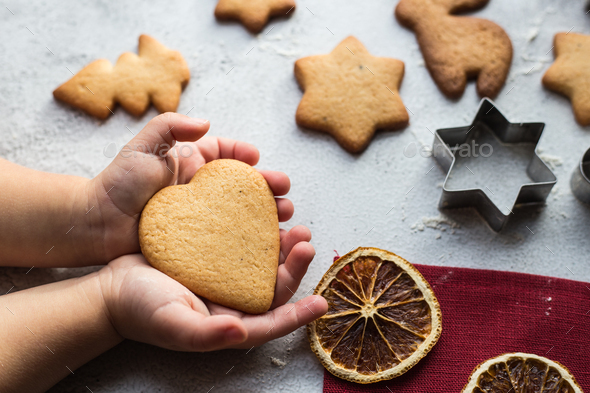 The child is holding a heart-shaped gingerbread in his hands - Stock Photo - Images