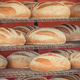 Fresh wholegrain loaves of rye or wheat bread on shelves in bakery. Vintage photo - PhotoDune Item for Sale