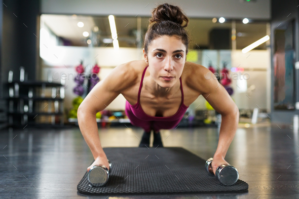 Woman doing push-ups exercise with dumbbell in a fitness workout - Stock Photo - Images