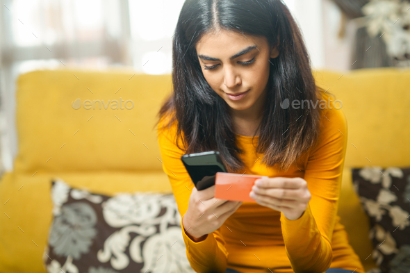 Woman shopping with smartphone paying with her credit card - Stock Photo - Images