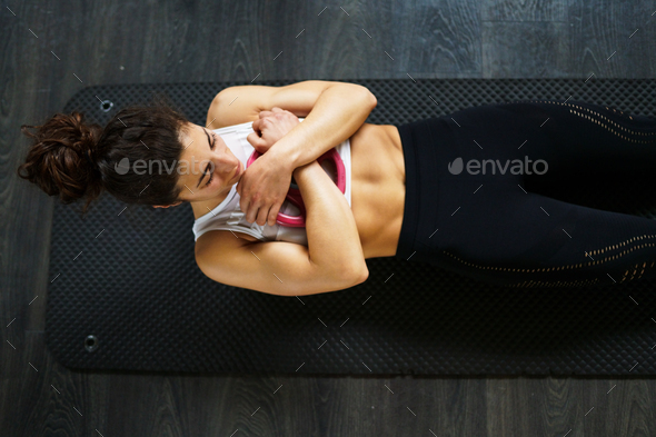 Young sportswoman on yoga mat doing situps in gym - Stock Photo - Images