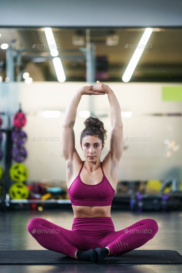 Young woman Doing Stretching Exercises on a yoga mat - Stock Photo - Images