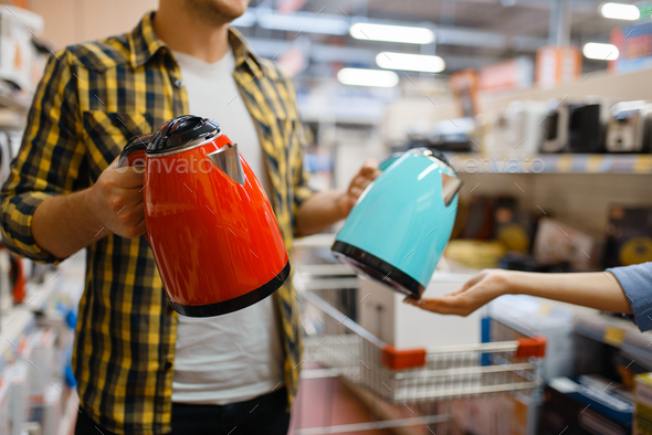 Couple choosing electric kettle, electronics store - Stock Photo - Images