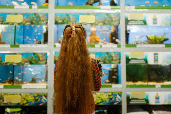 Girl looking on fishes in aquarium, pet store - Stock Photo - Images