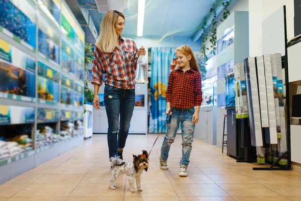 Mother with daughter walking in pet store - Stock Photo - Images