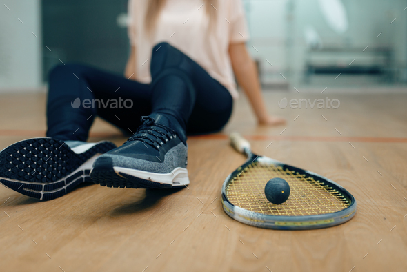 Player with squash racket and ball sits on floor - Stock Photo - Images
