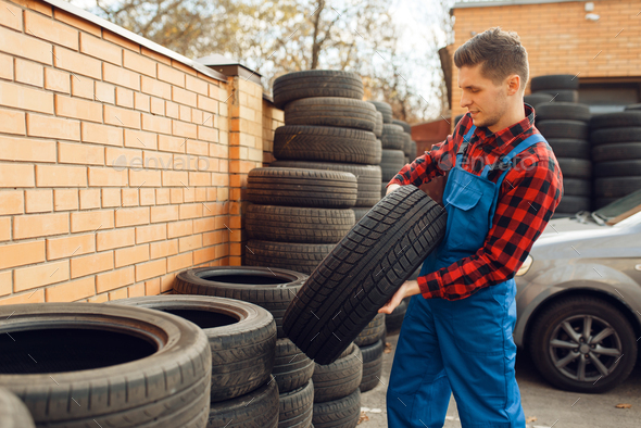 Male worker at the stack of tyres, tire service - Stock Photo - Images