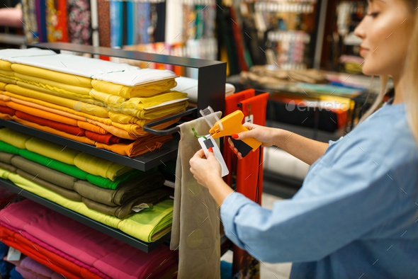 Female seller holds fabric in textile store - Stock Photo - Images