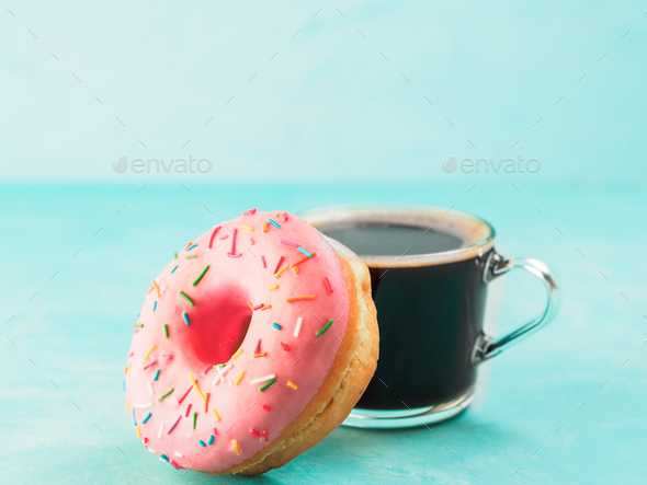 pink donut and coffee on blue background , copy space - Stock Photo - Images