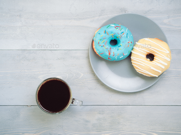 donuts and coffee on gray wooden background, copy space, top view - Stock Photo - Images