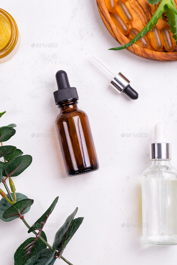 Beauty natural products with cosmetic cream, Omega-3 gel capsules, and serum in glass bottles on - Stock Photo - Images