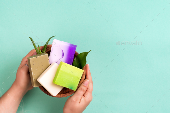 Woman hands holding natural organic color soap bar on blue background. Healthy lifestyle, beauty - Stock Photo - Images