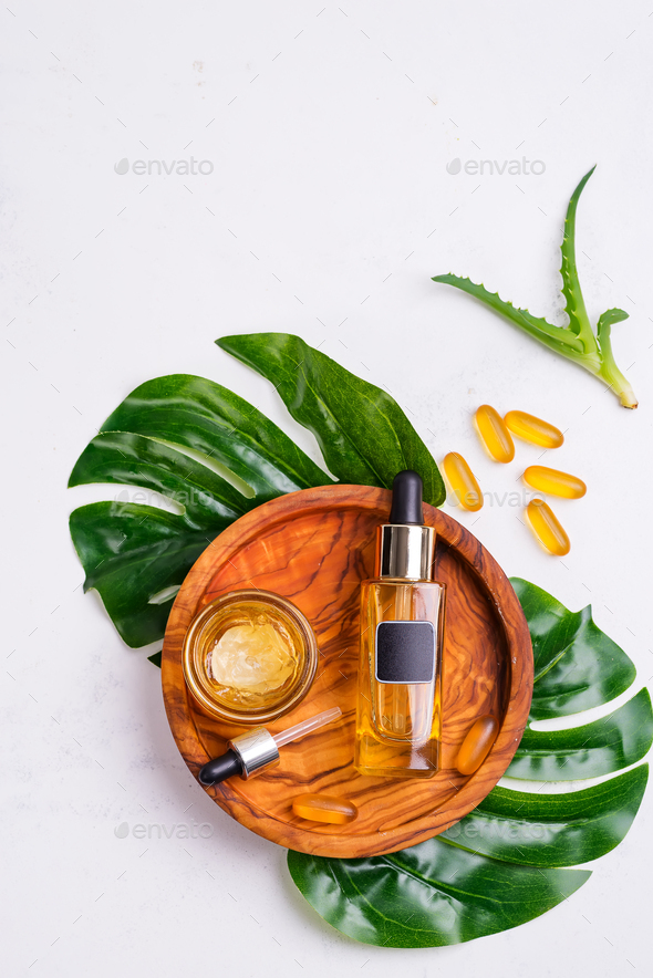 Cosmetic bottle with oil or hyaluronic acid and jar with mask for the face, Omega-3 gel capsules on - Stock Photo - Images