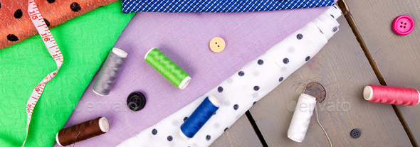 Banner of Items for sewing clothes. Sewing buttons, spools of thread and cloth. - Stock Photo - Images