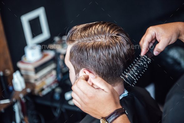 the master in the barbershop shaves and cuts the man - Stock Photo - Images