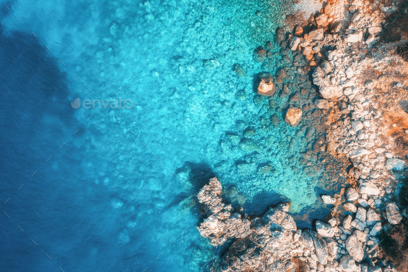 Aerial view of rocky beach and sea with transparent blue water - Stock Photo - Images