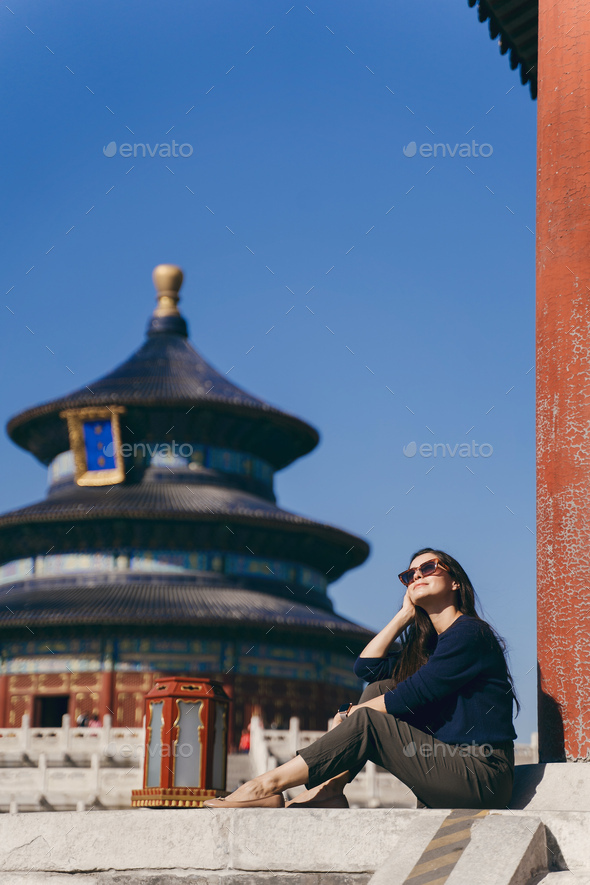 brunette girl sitting on the steps by temple of heven in China - Stock Photo - Images