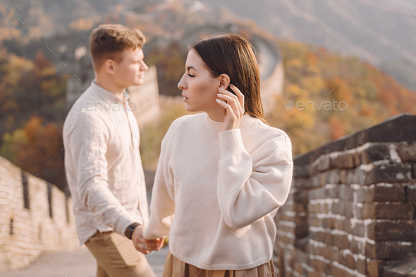 beautiful young couple holding hands and showing affection at the Great Wall of China - Stock Photo - Images