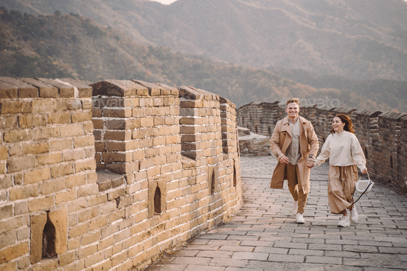 young couple running and twirling at the Great Wall of China - Stock Photo - Images