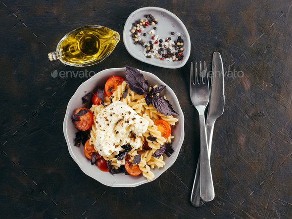 Pasta fusilli with cherry, mozarella and basil - Stock Photo - Images