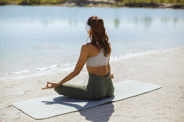 Woman Meditating in Yoga pose on the Beach - Stock Photo - Images