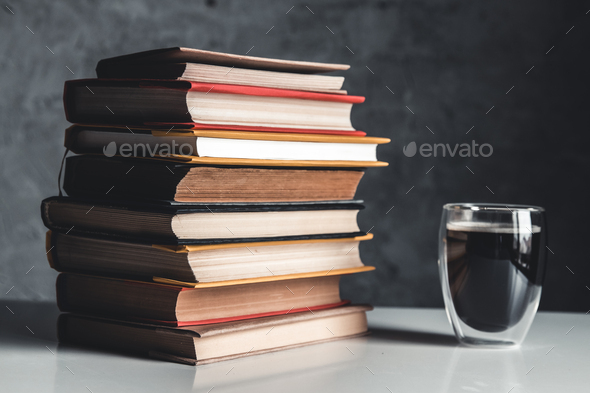 A cup of coffee near of stack of books on grey background - Stock Photo - Images