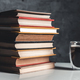 A cup of coffee near of stack of books on grey background - PhotoDune Item for Sale