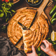 Human hands holding piece of Turkish borek pie with spinach - PhotoDune Item for Sale