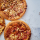 Three american style pizzas served on a table - PhotoDune Item for Sale