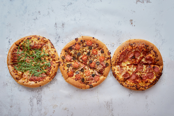 Three different kind of pizzas placed in a row on white rusty table - Stock Photo - Images