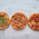 Three different kind of pizzas placed in a row on white rusty table - PhotoDune Item for Sale