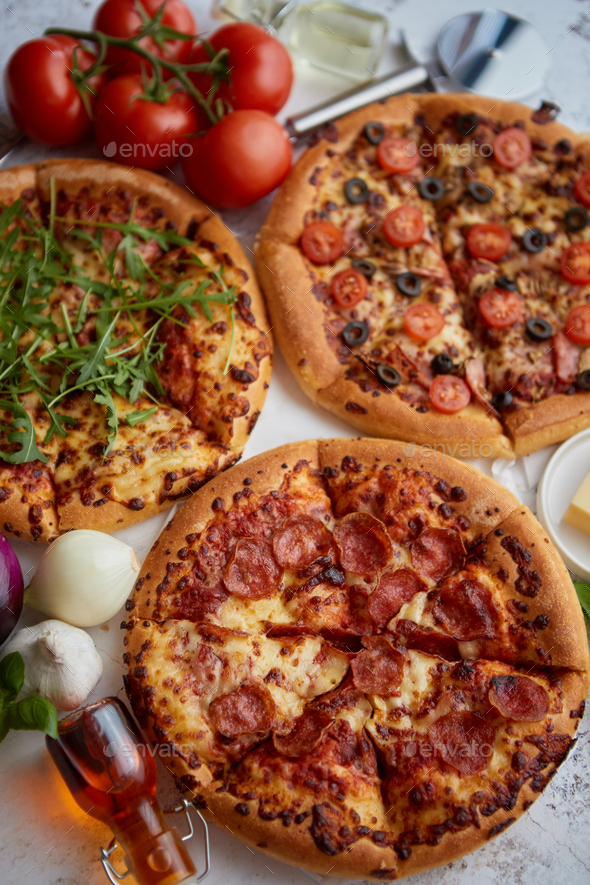 Three american style pizzas served on a table - Stock Photo - Images