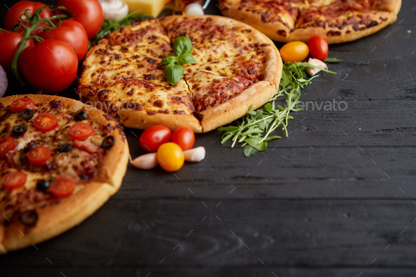 Freshly served, three various pizzas placed among tasty ingredients. Top view - Stock Photo - Images