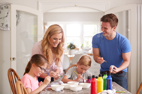 Parents With Children Sitting At Table Decorating Eggs For Easter At Home - Stock Photo - Images