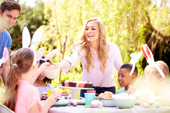 Parents With Children Wearing Bunny Ears Enjoying Outdoor Easter Party In Garden At Home - Stock Photo - Images
