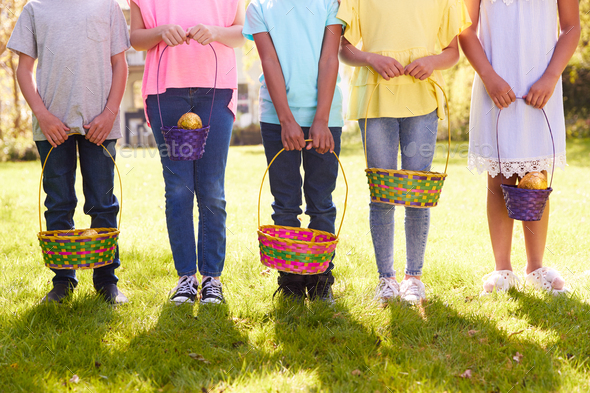 Close Up Of Five Children Holding Baskets On Easter Egg Hunt In Garden - Stock Photo - Images