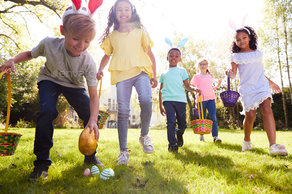 Group Of Children Wearing Bunny Ears Running To Pick Up Chocolate Egg On Easter Egg Hunt In Garden - Stock Photo - Images
