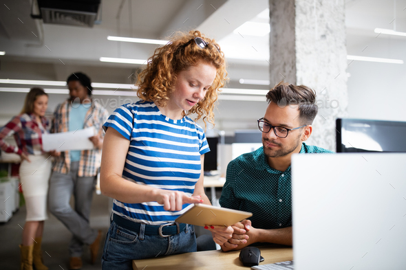 Programmers cooperating at IT company developing apps - Stock Photo - Images