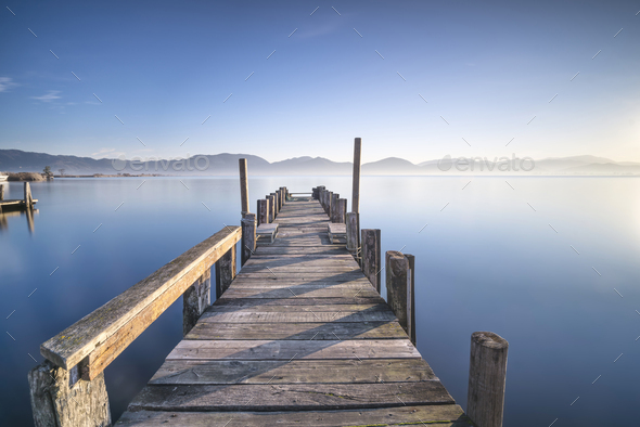 Wooden pier or jetty and lake at sunrise. Torre del lago Puccini Versilia Tuscany, Italy - Stock Photo - Images